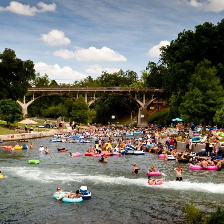 Sunny day with people tubing down a river under a bridge.